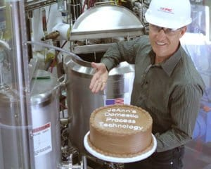 EPIC CEO John Schott displays a cake in front of a batch mixing system