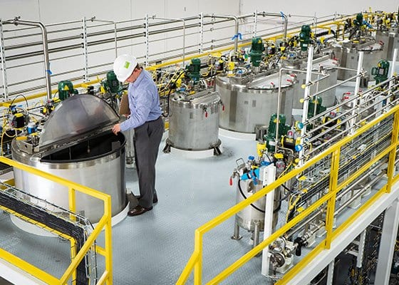 An engineer inspects a batch-mixing system