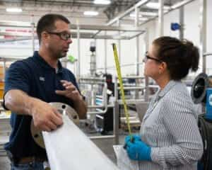 A craftsman and a quality control specialist discuss fabrication of a pharma process system