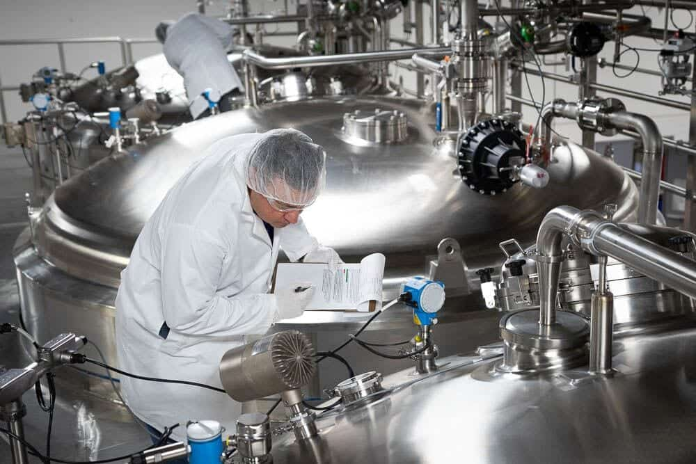 An operator of a pharmaceutical production plant inspects an EPIC hygienic process plant layout and piping design