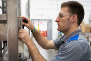 A skid manufacturer inspects a control box