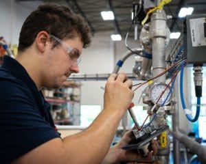 An electrician installs controls equipment on an industrial process system