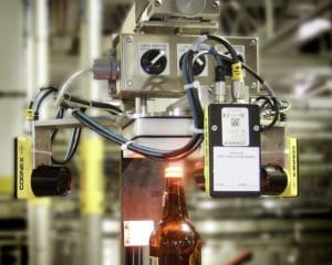 A packaging inspection system conducts a bottle inspection in a production plant